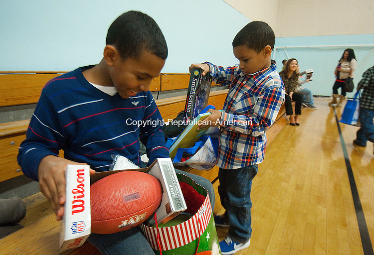 WATERBURY,  CT-010615JS02-Stacy Speaks, 11, left, of Waterbury and his brother Mekhi Speaks, 5, check out the gifts they received during the annual Three Kings Day ceremony Tuesday at the Hispanic Coalition, Inc. Waterbury. Jim Shannon Republican-American
