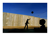 Ishak Amer (C) , 12, a Palestinian boy from the West Bank town of Masha, plays with his young brother Shadad, 3, football in the front yard of their home, in front of a security wall built by Israel, October 28, 2003. The house of the Amer's family is the only Palestinian house of Masha who was left on the Israeli sade of the new security fence, next to the Jewish settlement of Elkana. Photo by Quique Kierszenbaum