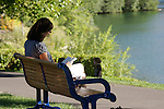 A woman uses her lunch hour to catch a little reading time at Riverwalk Park in Chelan, Washington.