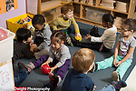 Preschool 2-3 year olds group of children doing ball rolling activity in pairs