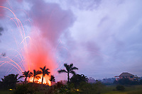 lava emanating from Kilauea Volcano, erupts from a fissure near a residence off Highway 132 between Pahoa and Kapoho in Puna, Big Island, Hawaii, USA, explosive eruptions blast chunks of hot lava hundreds of feet into the air (the two lights near the bottom of the frame are landscape lighting)