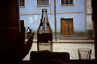 A Bolivian passes an afternoon near a small cafe in Quispe, Bolivia.