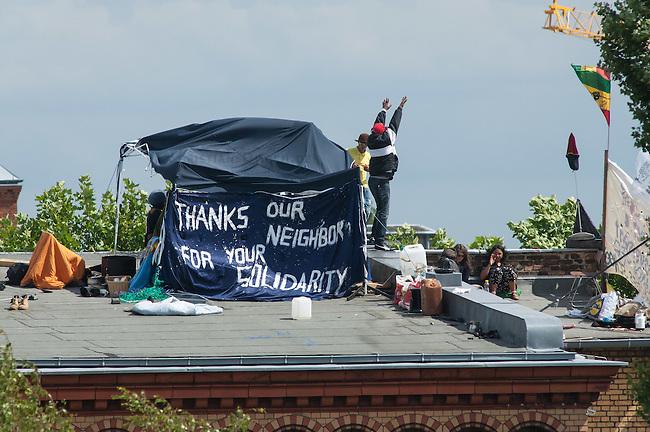 Fluechtlingsprotest auf dem Dach der Gerhard-Hauptmann-Schule in der Ohlauer Strasse in Berlin-Kreuzberg.<br /> Seit dem 24. Juni 2014 haben harren Fluechtlinge und deren Unterstuetzer auf dem Dach der Gerhard-Hauptmann-Schule aus. Sie hatten sich geweigert dem sog. &quot;Freiwilligen Umzug&quot; zu folgen, der vom Gruenen Bezirksstadtrat Hans Panhoff angeordnet worden war. Die Polizei war bei der als &quot;Umzug&quot; geschoenten Raeumung mit gezogenen Maschinenpistolen angerueckt.<br /> Baustadtrat Panhoff hat am 1. Juli 2014 die polizeiliche Raeumung des Schulgebaeudes beantragt. Einige der Fluechtlinge haben angekuendigt, im Fall der Raeumung vom Dach zu springen. &quot;Wir haben nichts mehr zu verlieren!&quot; sagen sie.<br /> Die Polizei hat seit dem 24. Juni mit ueber 1.000 Beamten saemtliche Strassen um die Schule abgeriegelt. Anwohner duerfen nur nach Personalienfeststellung in ihre Wohnungen, Geschaefte und Gewerbe koennen keine Kundschaft mehr empfangen. Anwohner die gegen das Vorgehen der Polizei protestieren werden von Beamten drangsaliert, geschlagen und verletzt. Mehrere Personen, darunter auch Kinder mussten zum Teil mit Kieferbruch ins Krankenhaus.<br /> 2.7.2014, Berlin<br /> Copyright: Christian-Ditsch.de<br /> [Inhaltsveraendernde Manipulation des Fotos nur nach ausdruecklicher Genehmigung des Fotografen. Vereinbarungen ueber Abtretung von Persoenlichkeitsrechten/Model Release der abgebildeten Person/Personen liegen nicht vor. NO MODEL RELEASE! Don't publish without copyright Christian-Ditsch.de, Veroeffentlichung nur mit Fotografennennung, sowie gegen Honorar, MwSt. und Beleg. Konto: I N G - D i B a, IBAN DE58500105175400192269, BIC INGDDEFFXXX, Kontakt: post@christian-ditsch.de<br /> Urhebervermerk wird gemaess Paragraph 13 UHG verlangt.]
