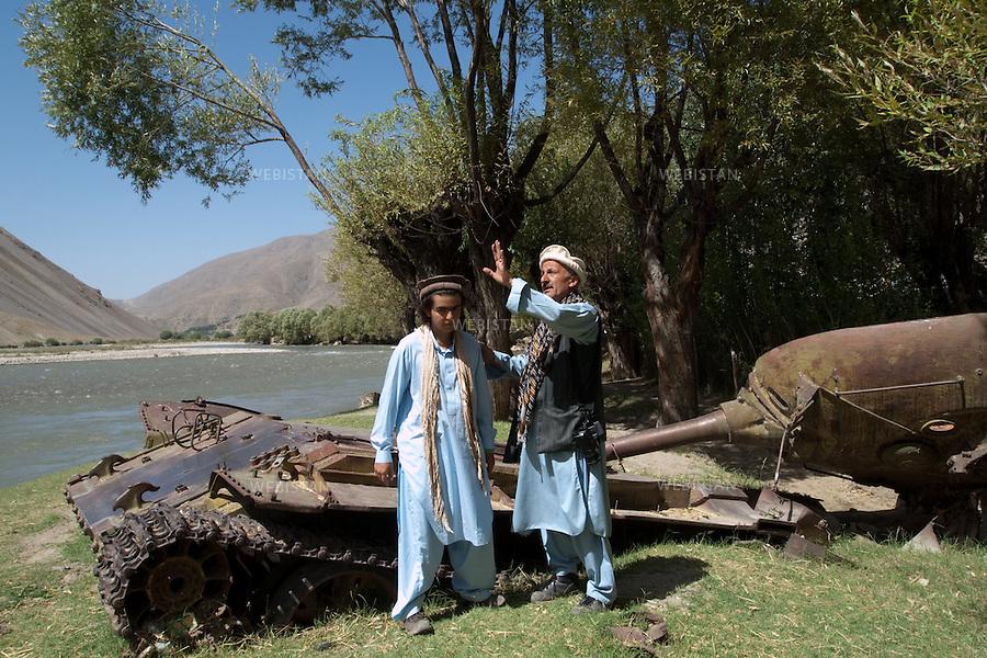 """AFGHANISTAN - VALLEE DU PANJSHIR - 18 aout 2009 : Riviere du Panjshir. Reza et Delazad Deghati devant la carcasse d'un char pris aux russes par les Moudjahidin du Commandant Massoud lors de leurs assauts pendant la guerre d'Afghanistan de 1979 - 1989. .La photographie appartient a la serie """"Il etait une fois l'Empire Russe"""". ..AFGHANISTAN - PANJSHIR VALLEY - August 18th, 2009 : Panjshir River. Reza and Delazad Deghati stand before the remnants of a Russian tank seized by Commander Massoud's mujahideen during the Afghan war of 1979-1989..The photograph is part of the series """"Once Upon a Time, the Russian Empire."""""""
