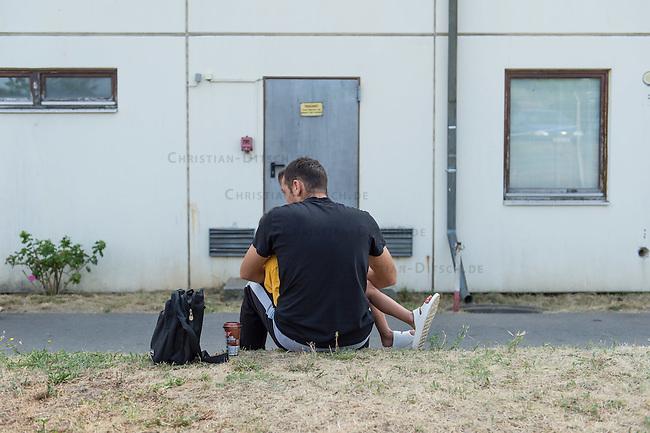 Zentrale Auslaenderbehoerde und BAMF-Aussenstelle in Eisenhuettenstadt.<br /> Bundesinnenminister Thomas de Maiziere und brandeburgs Ministerpraesident Dietmar Woidke besuchten am Donnerstag den 13. August 2015 die Zentrale Auslaenderbehoerde und BAMF-Aussenstelle in Eisenhuettenstadt. Sie liessen sich von Mitarbeitern die Situation in der Einrichtung zeigen und erklaeren, sprachen mit Fluechtlingen und besichtigten das auf dem Gelaende befindliche Abschiebegefaengnis.<br /> Der Besuch des Bundesinnenministers und des Ministerpraesidenten wurde von etwa 40 Journalisten begleitet.<br /> Im Bild: Ein Vater mit seinem vor einem der Wohngebaeude.<br /> 13.8.2015, Eisenhuettenstadt/Brandenburg<br /> Copyright: Christian-Ditsch.de<br /> [Inhaltsveraendernde Manipulation des Fotos nur nach ausdruecklicher Genehmigung des Fotografen. Vereinbarungen ueber Abtretung von Persoenlichkeitsrechten/Model Release der abgebildeten Person/Personen liegen nicht vor. NO MODEL RELEASE! Nur fuer Redaktionelle Zwecke. Don't publish without copyright Christian-Ditsch.de, Veroeffentlichung nur mit Fotografennennung, sowie gegen Honorar, MwSt. und Beleg. Konto: I N G - D i B a, IBAN DE58500105175400192269, BIC INGDDEFFXXX, Kontakt: post@christian-ditsch.de<br /> Bei der Bearbeitung der Dateiinformationen darf die Urheberkennzeichnung in den EXIF- und  IPTC-Daten nicht entfernt werden, diese sind in digitalen Medien nach &sect;95c UrhG rechtlich geschuetzt. Der Urhebervermerk wird gemaess &sect;13 UrhG verlangt.]
