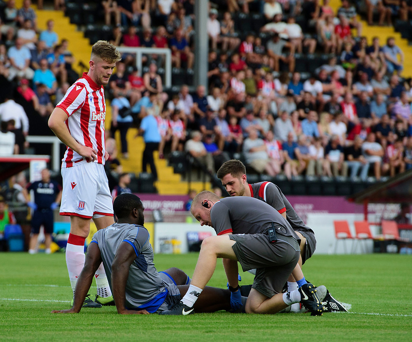 Lincoln City's John Akinde receives treatment for an injury from Lincoln City sports science and medicine assistant Luke Treadwell, centre, and Lincoln City's strength and conditioning/sports massage Kieran Walker<br /> <br /> Photographer Chris Vaughan/CameraSport<br /> <br /> Football Pre-Season Friendly - Lincoln City v Stoke City - Wednesday July 24th 2019 - Sincil Bank - Lincoln<br /> <br /> World Copyright © 2019 CameraSport. All rights reserved. 43 Linden Ave. Countesthorpe. Leicester. England. LE8 5PG - Tel: +44 (0) 116 277 4147 - admin@camerasport.com - www.camerasport.com