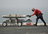"080611-N-7981E-270 ARABIAN GULF (June 11, 2008)- An Aviation Ordnanceman uses a ""skid"" to transport bombs to an aircraft on the flight deck of Nimitz-class aircraft carrier USS Abraham Lincoln (CVN 72). Lincoln is deployed to the U.S. Navy 5th Fleet area of responsibility to support Maritime Security Operations (MSO).  MSO help develop security in the maritime environment, which promotes stability and global prosperity.  These operations complement the counterterrorism and security efforts of regional nations and seek to disrupt violent extremists' use of the maritime environment as a venue for attack or to transport personnel, weapons or other material.  U.S Navy photo by Mass Communication Specialist 2nd Class James R. Evans (RELEASED)"