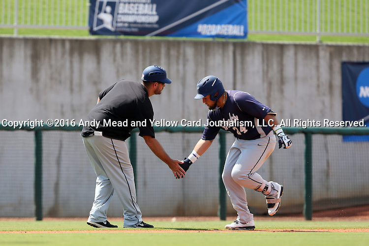 03 June 2016: Nova Southeastern's Brandon Gomez (24) slaps a low five with head coach Greg Brown (left) as he rounds third base after hitting a game-tying home run. The Nova Southeastern University Sharks played the Millersville University Marauders in Game 13 of the 2016 NCAA Division II College World Series  at Coleman Field at the USA Baseball National Training Complex in Cary, North Carolina. Nova Southeastern won the first game of the best of three Championship Series 2-1.