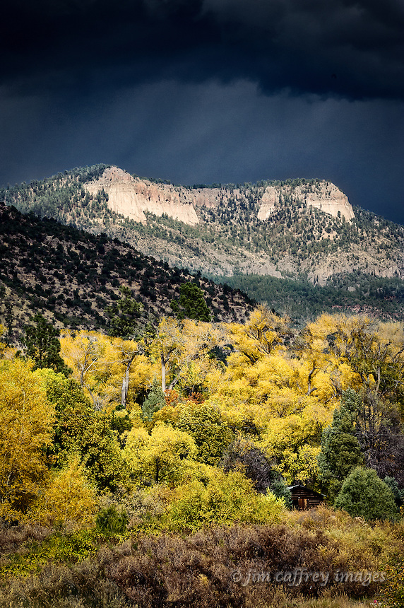 The sun peeks through a dark, stormy sky to illuminate a rincon in San Diego Canyon in the Santa Fe National Forest north of Jemez Springs, New Mexico