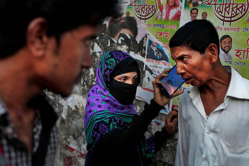 A Bangladeshi Muslim woman helps her husband to talk over the cellphone, as a man watches them and walks past on a road in Dhaka, Bangladesh.