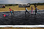 Kids on a wet canvas, which protesters have laid at Adolam Park, Israel, to simulate a river of black oil. Environmental organizations protest against IEI's plan to drill the region searching for shale oil.
