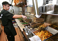 Jose Gonzales uses deep-fat fryers to cook fries and onion rings at a Jack-in-the-Box quick-service restaurant in Redmond, Washington.