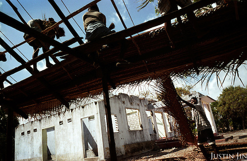 Fishermen rebuild a thatched house destroyed by the tsunami in Pallai, a village in the northeastern coast of Sri Lanka, an area ravaged also by civil war. .The December 26, 2004 tsunami killed around 40,000 people along Sri Lanka's southern, eastern and northern shores, tearing thousands of families apart. .The bulk of the dead were women and children - husbands lost young brides and around 4,000 children lost one or both parents. .Even before the tsunami struck, people here in the northeast had already been displaced four times by the Tigers' two-decade war for autonomy. .In some places, the scars of war and the tsunami have become one. Remnants of walls torn down by waves are pockmarked with bullet holes and shrapnel from shells fired before a 2002 ceasefire plunged a civil war that killed over 64,000 people into limbo. ..Picture taken March 2005 by Justin Jin