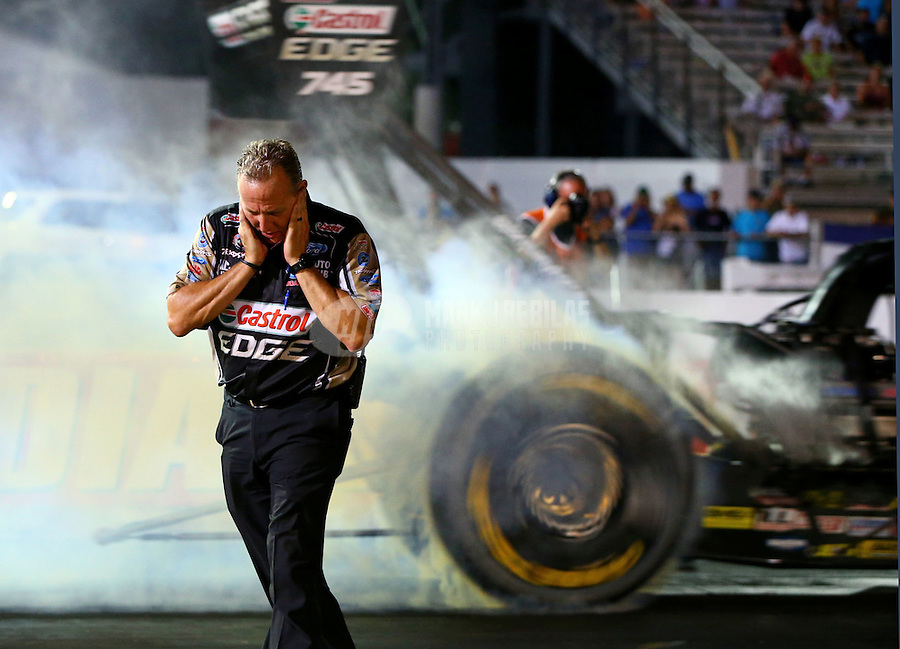 Aug 29, 2014; Clermont, IN, USA; Todd Smith , crew chief for NHRA top fuel driver Brittany Force holds his ears as she does a burnout during qualifying for the US Nationals at Lucas Oil Raceway. Mandatory Credit: Mark J. Rebilas-USA TODAY Sports