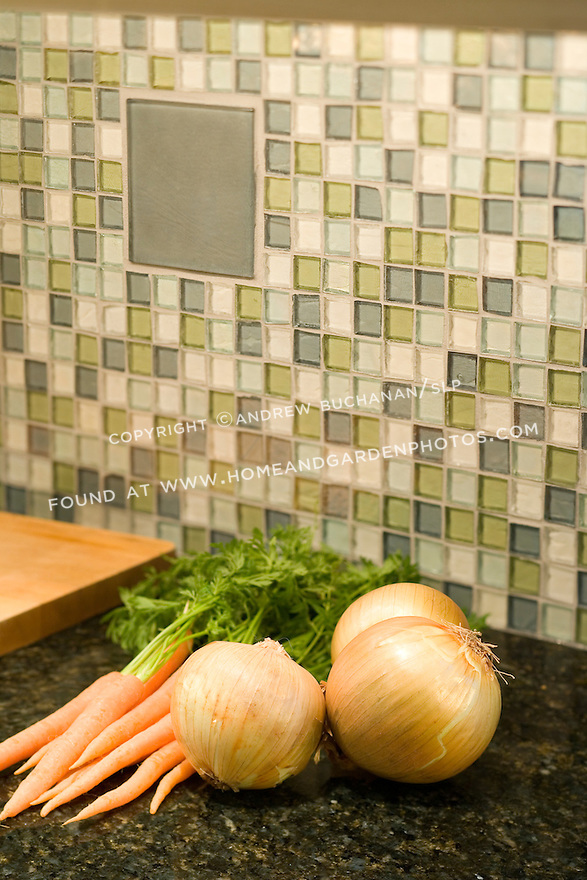 Detail shot of vegetables atop a kitchen counter with a beautiful recycled glass tile mosaic as a backsplash.  Building products made from recycled, salvaged, and/or environmentally friendly materials can be good looking, as well as good for the environment.