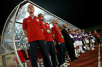 The United States' Thomas Rongen and the coaching staff listen to the Cameroon national anthem before the FIFA Under 20 World Cup Group C Match between the United States and Cameroon at the Mubarak Stadium on September 29, 2009 in Suez, Egypt.