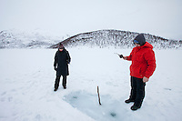 Couple ice- fishing on frozen lake in the Arctic Circle on Ringvassoya Island in the region of Tromso, Northern Norway