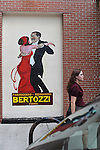 A woman walks passed a vintage Italian poster painted on the side of Treasure Island, the largest grocery store in Old Town, on Wells Street in Chicago, Illinois on June 19, 2009.