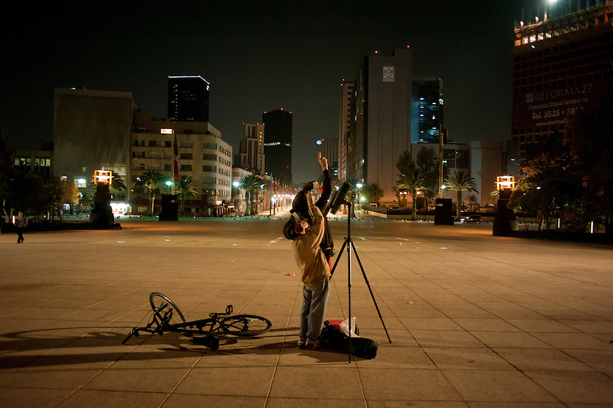 Looking at the stars with a telescope at the Monumento a la Revolucion. Night bicycle rides,  Mexico City.