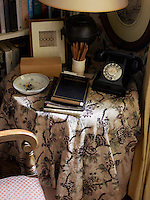 An old-fashoined black telephone, address book and ashtray on top of the round telephone table which is covered in a pretty floral cloth