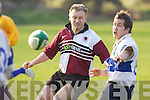 Tralees Cian OSullivan spins the ball out as Daithi OConnor of the pre-2000 Tralee team eyes up the tackle.