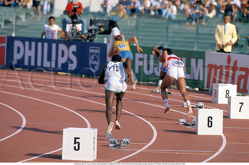 A rear view of athletes sprinting out of their starting blocks, SPRINT START. World Athletics Championships, Rome, 870. Photo: Richard Francis/Action Plus....1987.athletics sprint sprinter sprinting.woman.track and field.blocks numbers.runners sprinters.female