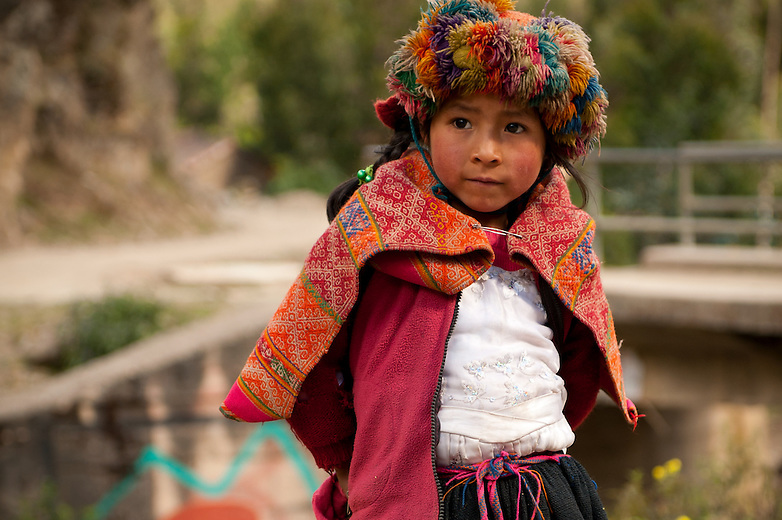 Located in the Andes town of Huilloc, a young Peruvian girl displays her colorful, woven clothes that were made in her weaving community. She wears an embroidered wrap around her clothing and a fancily decorated hat as well. The daily life in this village is revolved around the tradition of weaving. Kids begin learning how to use the back strap loom at a young age so that they can assist in the weaving and spinning process in their community.