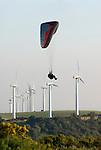Paraglider soaring with wind turbines in background.Andalucia,Spain.
