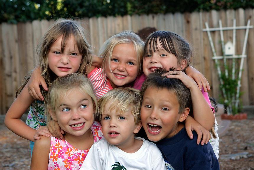 A portrait of six cousins in a backyard.