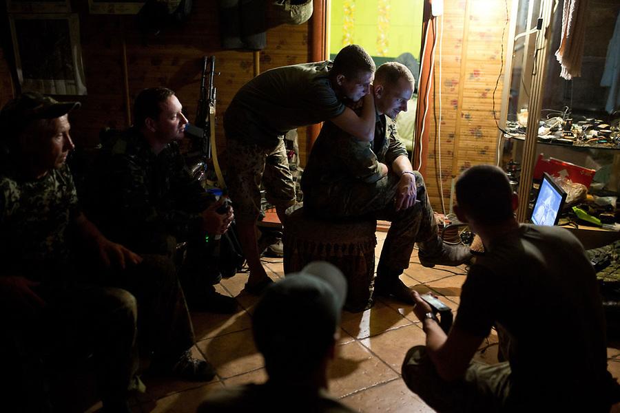 UKRAINE, Pisky: Dan and his comrades are watching a video on a laptop during the evening. If they are not on night mission, all the unit stay inside the rear base as snipers and shelling are more constant at night. <br /> <br /> <br /> UKRAINE, Pisky: Dans la soir&eacute;e, Dan et ses camarades regardent une vid&eacute;o sur un ordinateur. S'ils ne sont pas en mission de nuit, ils doivent rester &agrave; l'int&eacute;rieur de la base arri&egrave;re car les tireurs d'&eacute;lite et  bombardements sont plus constants dans la nuit.