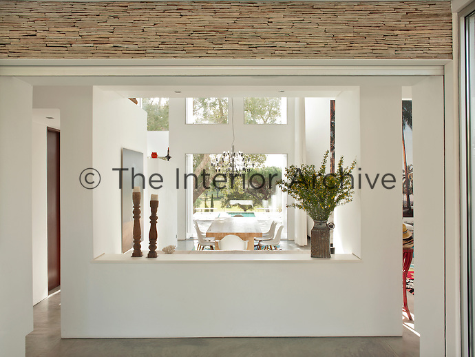 A view into a contemporary dining room space with a simple pine wood table and white Eames dining chairs.