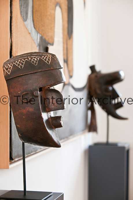A Lwalu on the left and a Ba-Bindji on the right, Congo masks displayed on stands with an abstract painting by Conrad Marcarelli