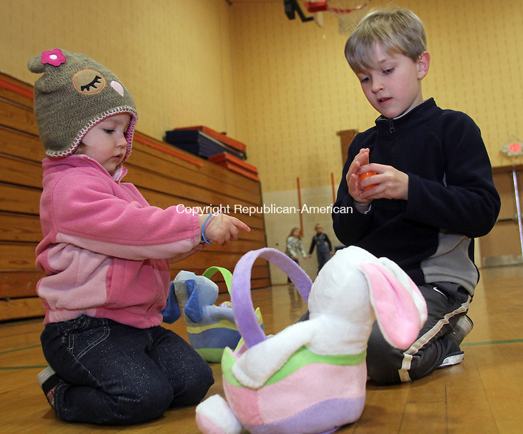 Winsted, CT-032313MK10  (from left) Two year old Annabelle Albert and her brother Christopher Albert (6) look over the surprises they found in the eggs they collected during the annual easter egg hunt at Person Middle School in Winsted on Saturday morning.  Tricia Twomuy, parks and recreation director, said that volunteers placed 1500 eggs for the activity.  Approximately 150 children participated in two different aged group hunts.  One was for toddlers to four years and one for five to eight year olds. Michael Kabelka Republican American