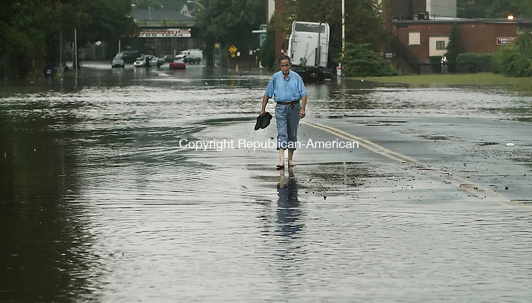 WATERBURY,  CT 17 September 2005 -091705BZ17- Waterbury resident Remzi Ciko took off his shoes and socks to make his way through the floodwater on Freight Street in Waterbury after heavy rain soaked the area Saturday afternoon.  Ciko said he was on his way to get a coffee but couldn't make it to the shop.<br /> Jamison C. Bazinet / Republican-American