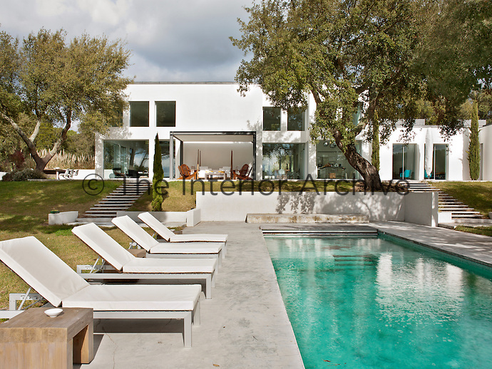 The exterior of a contemporary white house. Steps lead down from a terrace to a swimming pool set in the garden.