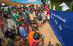 Children crowd around a RARE puppet show, starring a manta ray, Papagaran island, Komodo National Park