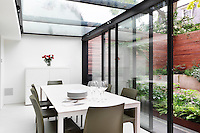 A modern conservatory extension with a glass roof and sliding glass doors, which give access to the garden. The room is furnished with a white dining table and grey chairs.