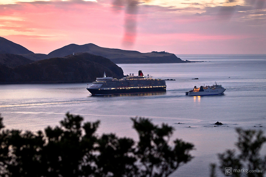 The Queen Elizabeth dwafs the Interisland ferry as it sails into Wellington Harbour at sunrise. The ship itself weighing 90,900 tons is as tall as a 21 story building and is the largest ship to date to arrive in Wellington Harbour
