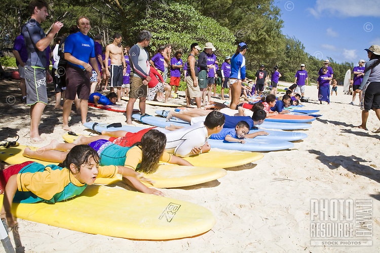 Kids learning how to surf at a charity event in Waimanalo
