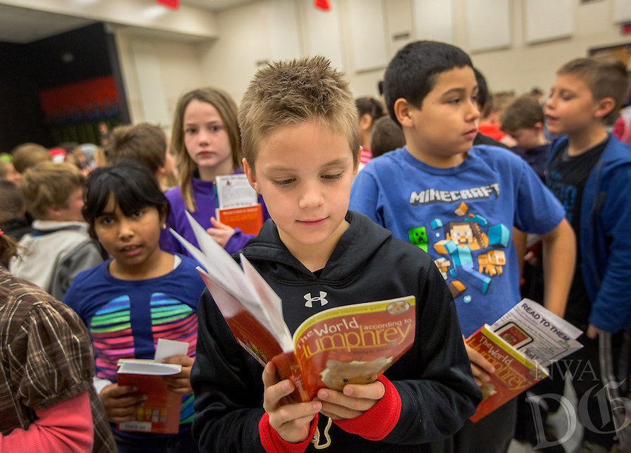 NWA Democrat-Gazette/JASON IVESTER --01/30/2015--<br /> Apple Glen Elementary third-grader Carson Harrell looks over the first couple pages in the book, &quot;The World According to Humphrey,&quot; during the kickoff for One District, One Book on Friday, Jan. 30, 2015, at the Bentonville school. Kindergarten through fourth-graders in the school district will read the same book with their families.