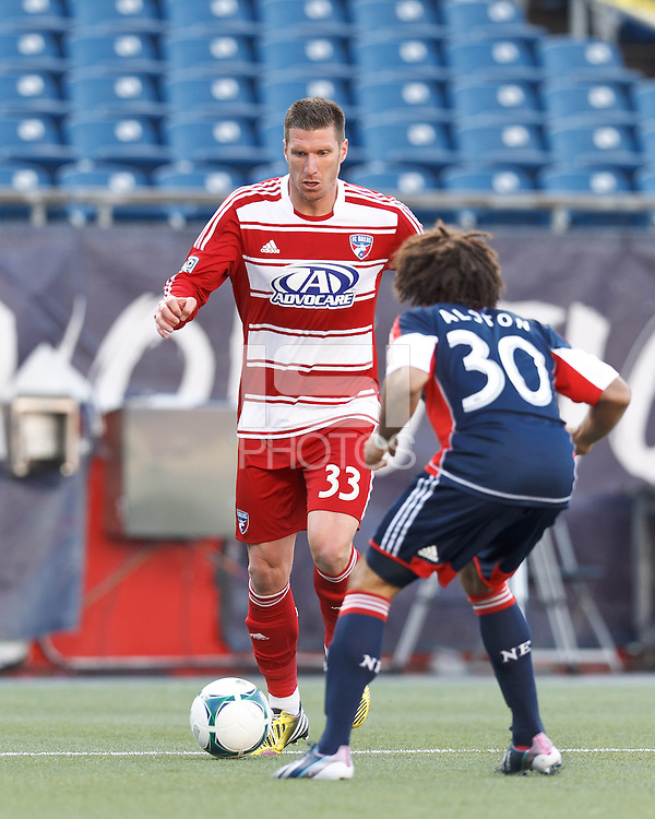 FC Dallas forward Kenny Cooper (33) dribbles. .  In a Major League Soccer (MLS) match, FC Dallas (red) defeated the New England Revolution (blue), 1-0, at Gillette Stadium on March 30, 2013.