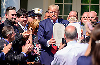 United States President Donald J. Trump holds up the bill after signing H.R. 1327, an act to permanently authorize the September 11th victim compensation fund, in the Rose Garden of the White House in Washington, DC on Monday, July 29, 2019. <br /> Credit: Ron Sachs / Pool via CNP/AdMedia
