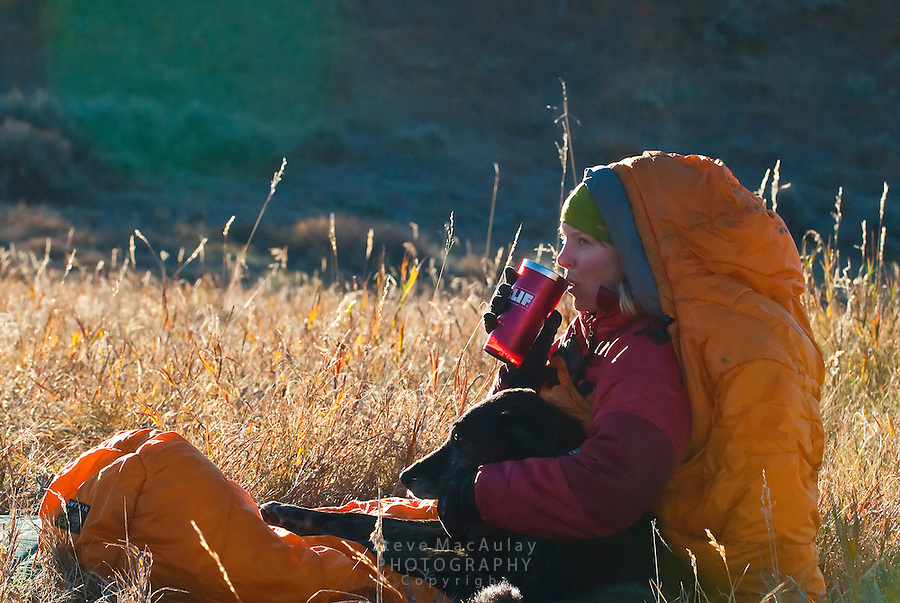 Woman enjoying cup of coffee on cold fall morning, Fall camping in Grand Teton National Park, Wyoming
