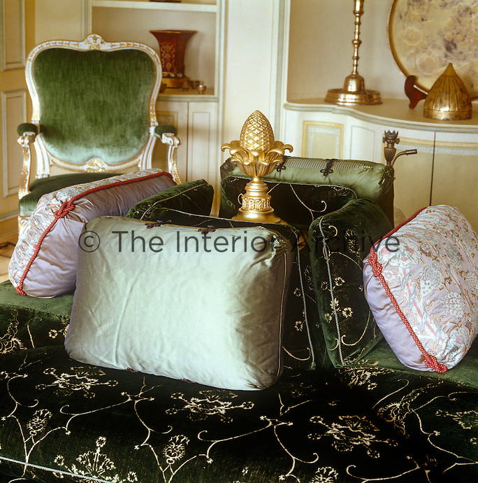 The green sitting room is furnished with a square conversation piece covered in cut velvet and topped with a gilt acorn
