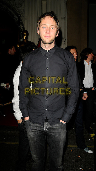 JAMES REDMOND.The Select Model Management Oscars Party, Mahiki nightclub, Dover St., London, England..February 22nd, 2009.half 3/4 length black shirt hands in pockets stubble facial hair beard jeans denim .CAP/CAN.©Can Nguyen/Capital Pictures.