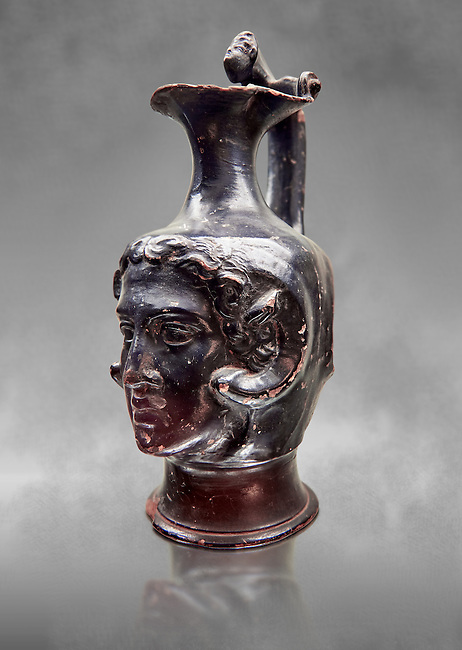 Etruscan bucchero jug with a face,  National Archaeological Museum Florence, Italy, grey art background