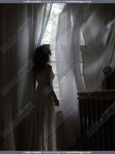 Artistic dramatic photo of a young woman in a dress standing by a window with flying in the wind curtains in a dark room of a house