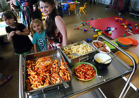 Pictured: Young children are served hot food at St Teilo Church in Clase, Swansea, UK. Friday 25 August 2017<br /> Re: Free food for children story, Swansea, Wales, UK.