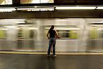 Mulher aguardando a parada do trem do metrô, atrás da faixa amarela, na plataforma da estação.