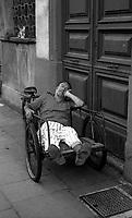 Roma  .Un  uomo dorme su un triciclo in Via dei Mille.Rome  .A man sleeps on a tricycle